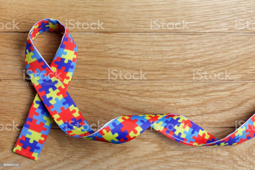 World Autism awareness and pride day or month with Puzzle pattern ribbon on wooden background. royalty-free stock photo