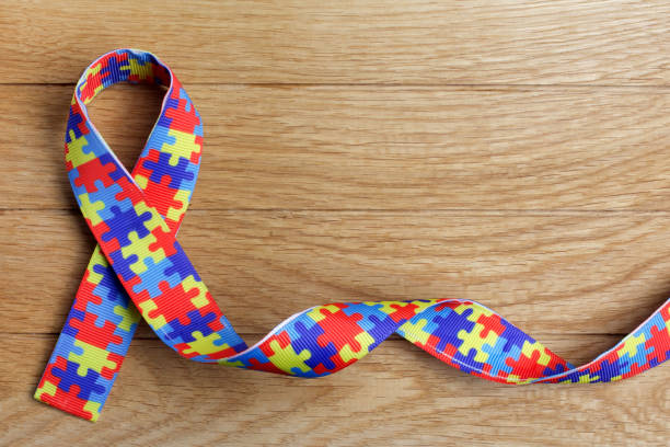 World Autism awareness and pride day or month with Puzzle pattern ribbon on wooden background. stock photo