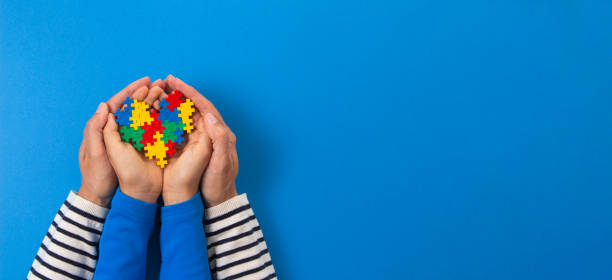 welt-autismus-bewusstseintag-konzept. erwachsene und kind hände halten puzzle herz auf hellblauem hintergrund - autismus stock-fotos und bilder