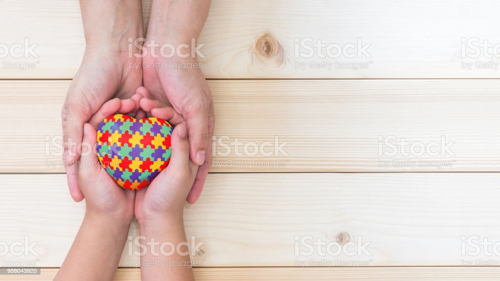 World Autism Awareness day concept with puzzle or jigsaw pattern on heart with autistic child's hands supported by nursing family caregiver stock photo