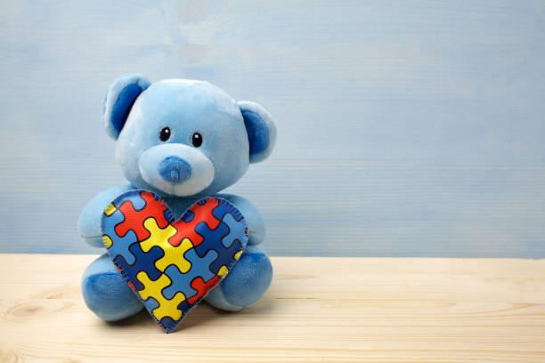 World Autism Awareness Day, Konzept mit Teddybär hält Rätsel oder Puzzlespiel auf dem Herzen – Foto