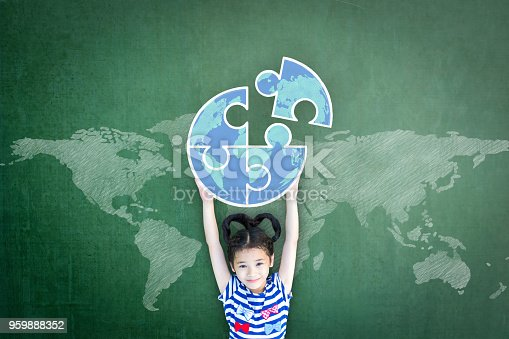 istock World autism awareness day education concept with girl kid's raising world globe in puzzle pieces on doodle chalkboard 959888352