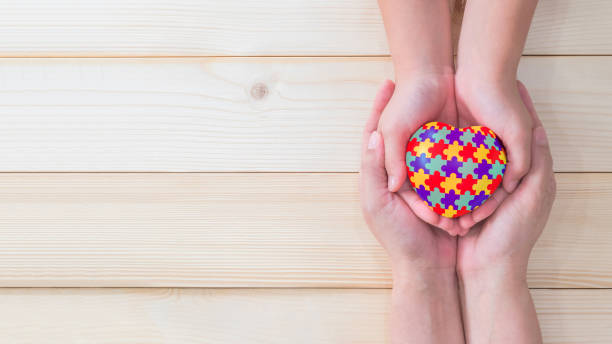 World Autism Awareness day, mental health care concept with puzzle or jigsaw pattern on heart with autistic child's hands supported by nursing woman, family caregiver person or parenting mother stock photo
