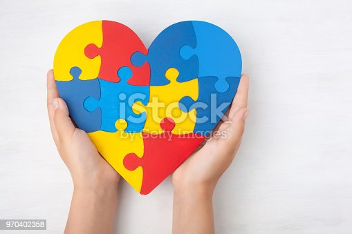 istock World Autism Awareness day, mental health care concept with puzzle or jigsaw pattern on heart with child's hands 970402358