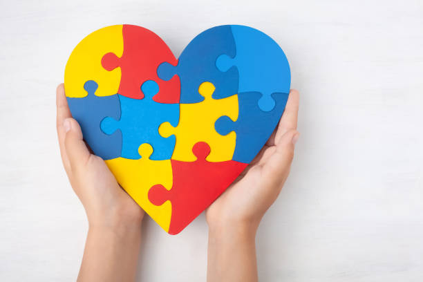 World Autism Awareness day, mental health care concept with puzzle or jigsaw pattern on heart with child's hands World Autism Awareness day, mental health care concept with puzzle or jigsaw pattern on heart with child's hands on white wooden background autism stock pictures, royalty-free photos & images