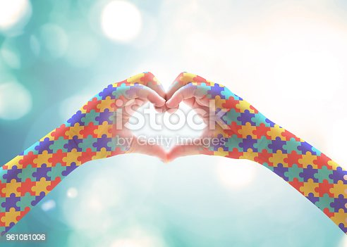 istock World Autism Awareness day, mental health care concept with puzzle jigsaw pattern on heart shape kid's hands for supporting autistic child medical charity campaign 961081006