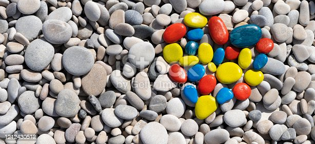 World autism awareness day. Top view to white beach stones with colorful heart made of painted stones.