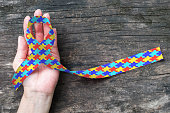 World Autism awareness day WAAD, April 2: Colorful Puzzle fabric ribbon logo color splashed on human hand background raising public support campaign on people's life living w/ mental health illness