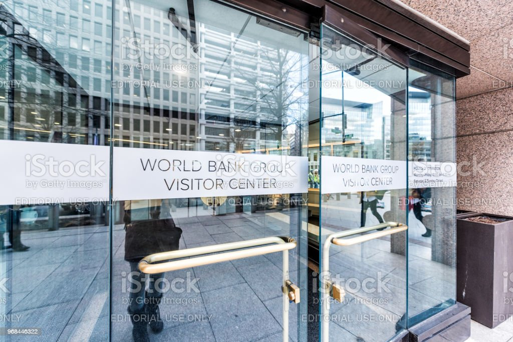 World Bank Group Vistor Center with gift shop to public sign doors in winter, window, entrance to building, people pedestrians walking on street sidewalk reflection stock photo