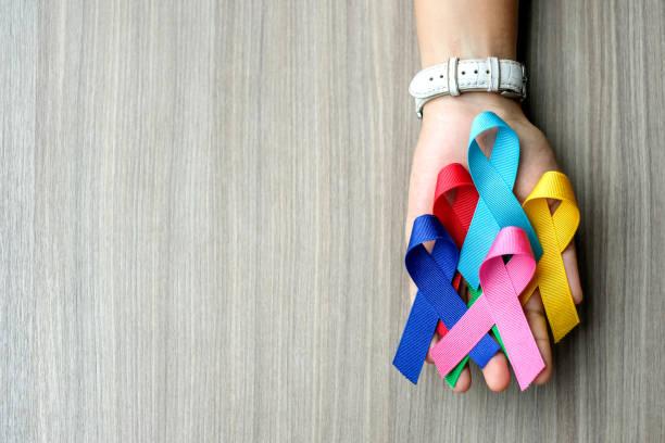 världscancerdagen (4 februari). färgglada medvetenhet band; blå, röd, grön, rosa och gul färg på trä bakgrund för att stödja människor som lever och sjukdom. sjukvårds-och medicin konceptet - blue yellow band bildbanksfoton och bilder