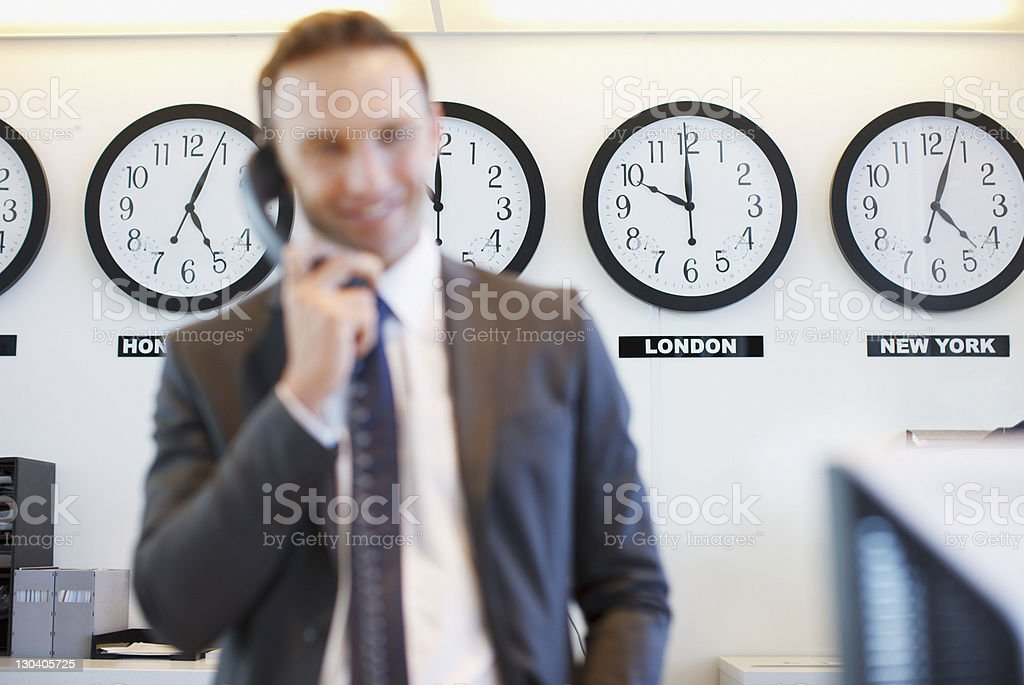 World clocks behind businessman in office stock photo