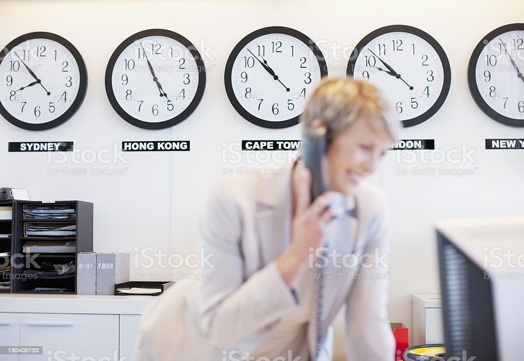 World clocks behind businesswoman in office stock photo