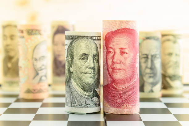 world economy and forex / foreign currency exchange concept : rolled up scroll of usd us dollar and cny chinese yuan banknotes with portrait of benjamin franklin and mao zedong on a square chessboard. - политика и правительство стоковые фото и изображения