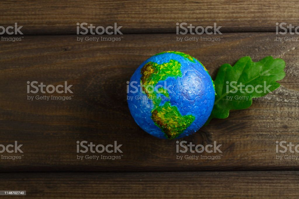 Globe with green oak leaf on a background of brown wooden boards.