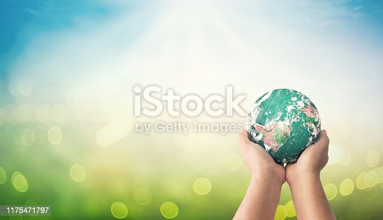 Human hands holding earth global on blurred green nature background. Elements of this image furnished by NASA