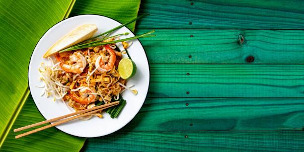 mundialmente famosa receta tailandesa de fideos tailandeses con palillos en un plato y hoja de plátano sobre un fondo de mesa de madera vieja de color turquesa. - comida tailandesa fotografías e imágenes de stock