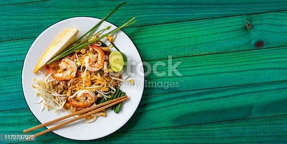 Pad Thai noodles with prawn are a world-famous delicacy, here, this colorful traditional dish is photographed directly above on a banana leaf on a textured wooden, colorful, vibrant turquoise background table.