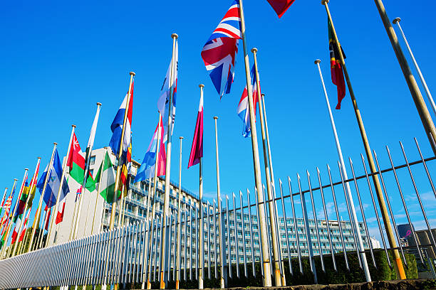 world flags in front of unesco headquarters in paris, france - unesco foto e immagini stock