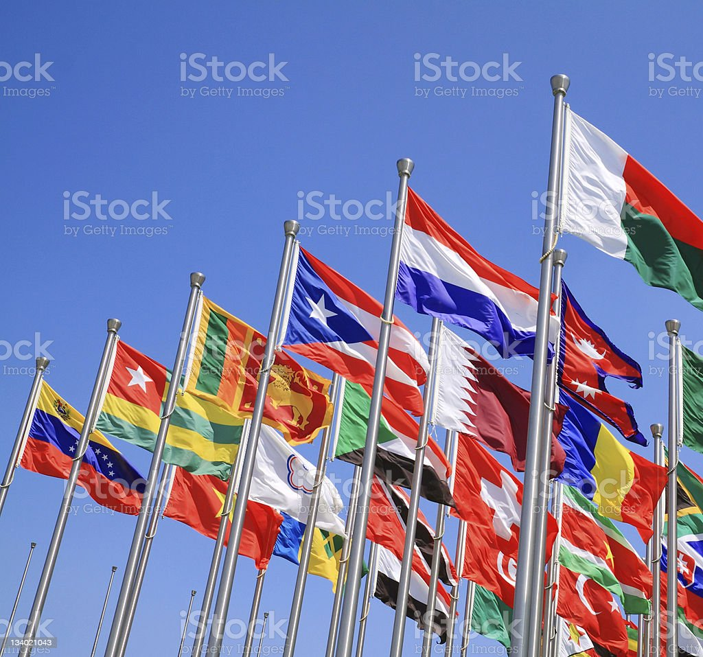 World flags on poles waving in the sky stock photo