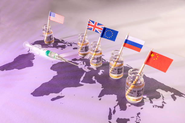 World globe map with country flags and vials for the global SARS/COVID pandemic vaccine war, with vaccine hoarding, restricting equal access to vaccines across the world, counteracted by the Covax programme and global vaccine alliance stock photo