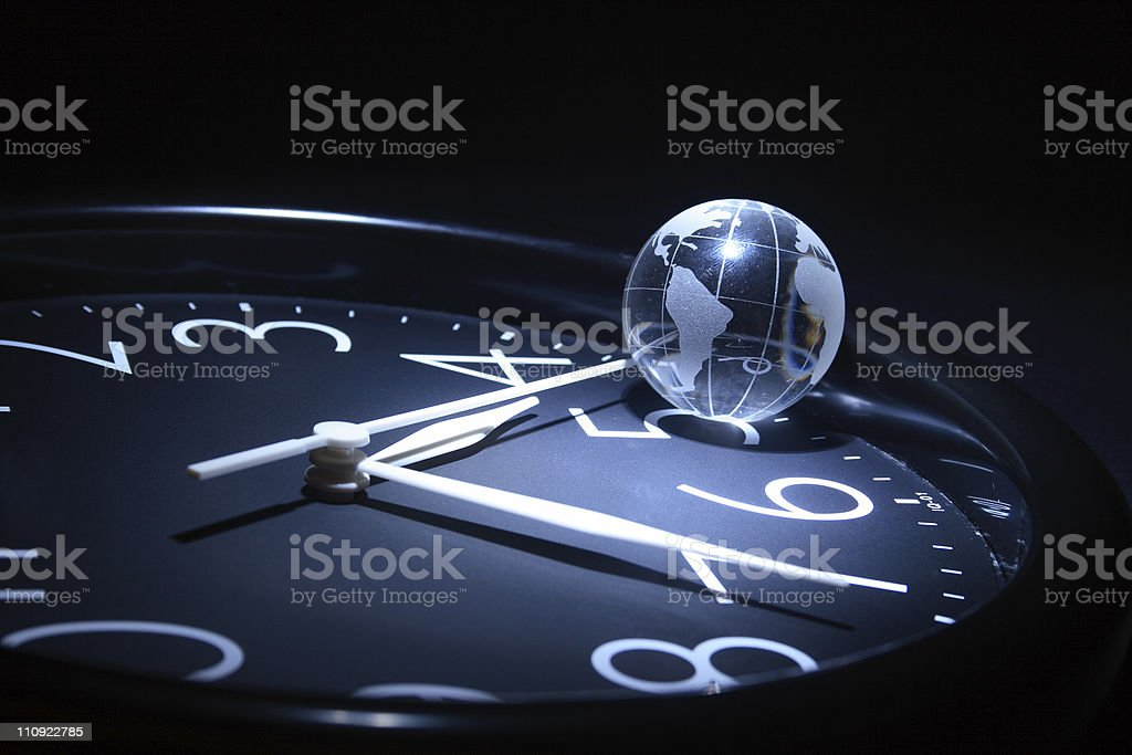 World globe resting on clock showing time stock photo