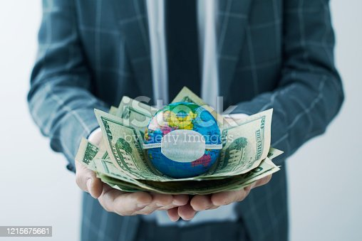 businessman holding a world globe with a protective mask on top of a handful of dollar bills, depicting the economic consequences of the coronavirus pandemic or of the pollution and climate change