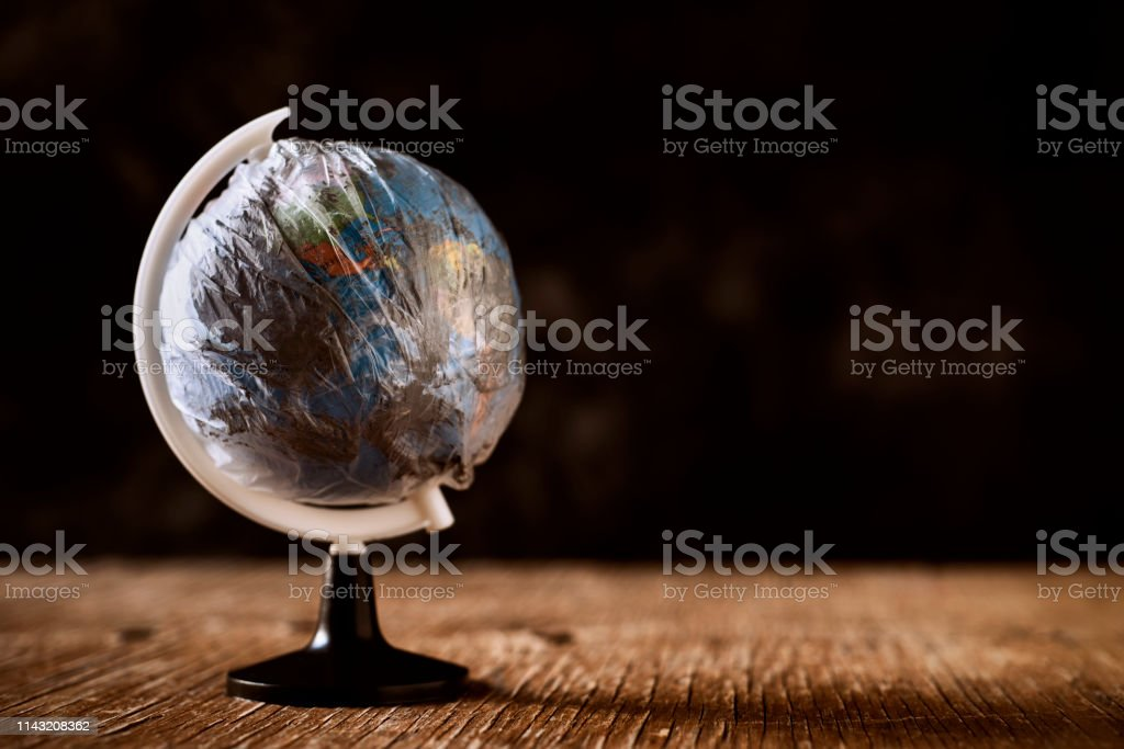 world globe wrapped in a dirty plastic a world globe wrapped in a dirty plastic, on a rustic wooden surface, against a dark background, depicting the air pollution, the excess of plastic waste on our planet or the greenhouse effect Air Pollution Stock Photo