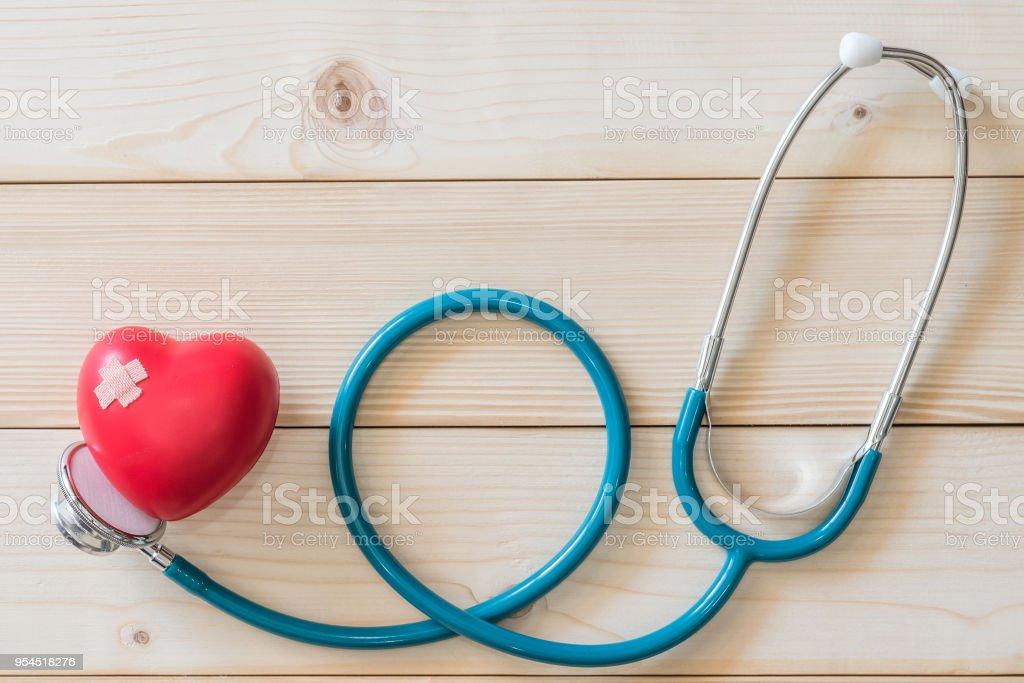 Campaña del día mundial de la salud con rojo amor corazón con vendaje y estetoscopio del médico, concepto de primeros auxilios - foto de stock