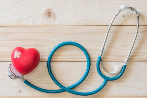 World health day campaign with red love heart  with cross bandage and medical doctor's stethoscope, first aid concept stock photo