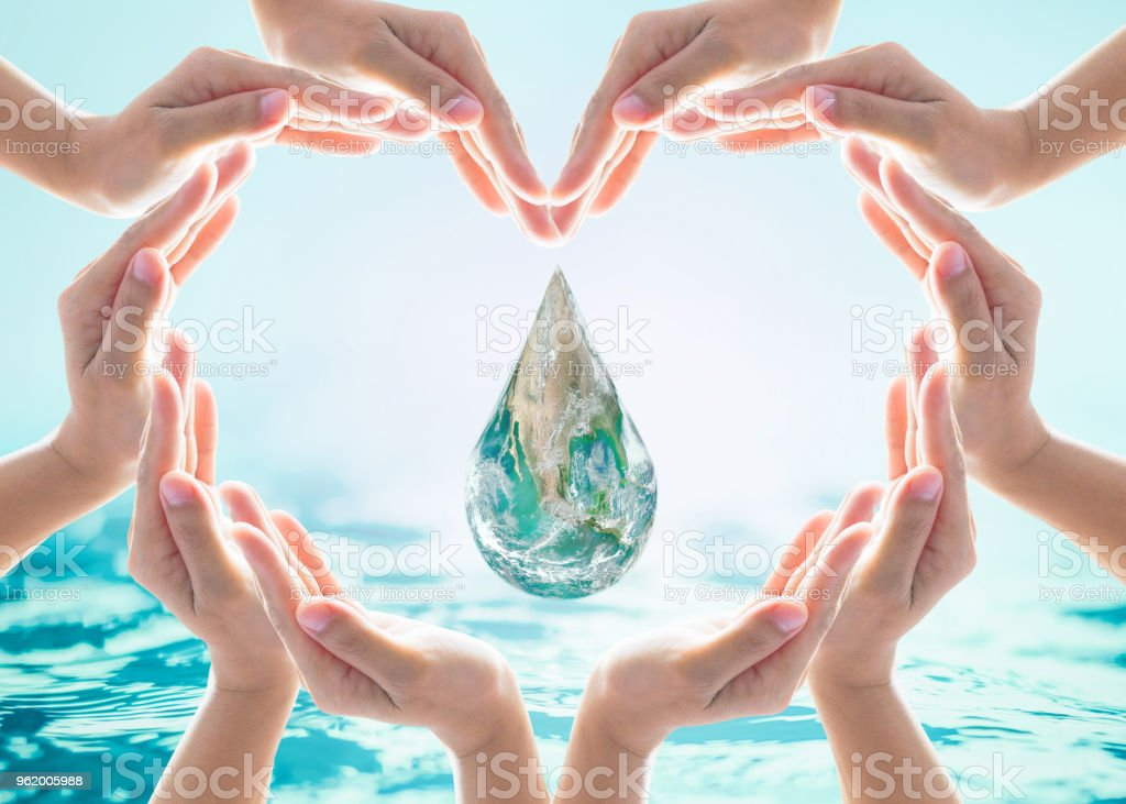 World heart day and environmental protection concept with earth water drop in community volunteer's hands. Element of this image furnished by NASA stock photo