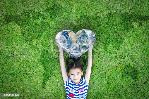 istock World heart day concept and well being health care campaign with smiling happy kid on eco friendly green lawn. Elements of this image furnished by NASA 968084066
