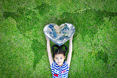 World heart day concept and well being health care campaign with smiling happy kid on eco friendly green lawn. Elements of this image furnished by NASA