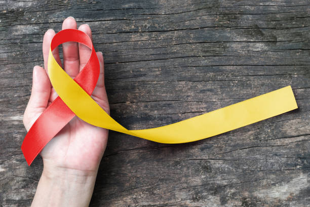 World hepatitis day and HIV/ HCV co-infection awareness with red yellow ribbon  (isolated  with clipping path) on person's hand support and old aged wood stock photo