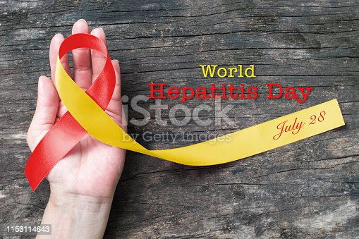 istock World hepatitis day awareness with red yellow ribbon  (isolated  with clipping path) on person's hand support and old aged wood 1153114643