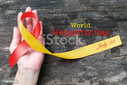 istock World hepatitis day awareness with red yellow ribbon  (isolated  with clipping path) on person's hand support and old aged wood 1159495094