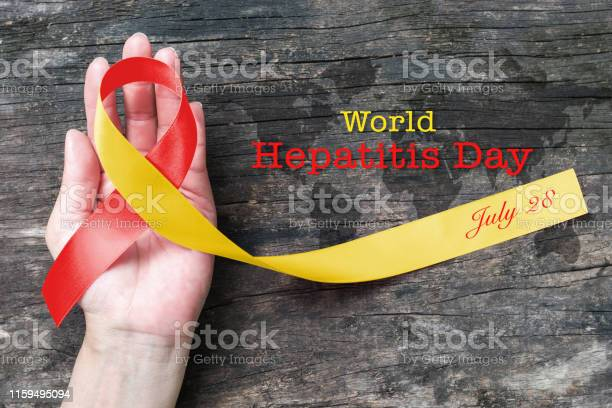 World Hepatitis Day Awareness With Red Yellow Ribbon On Persons Hand Support And Old Aged Wood Stock Photo - Download Image Now