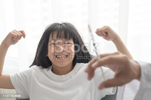 917598714istockphoto World immunization week and International HPV awareness day concept. Strong happy healthy Asia kid girl smiling getting vaccination for influenza or flu shot or HPV prevention with doctor pediatrician's hand holding medical syringe in hospital 1127762696