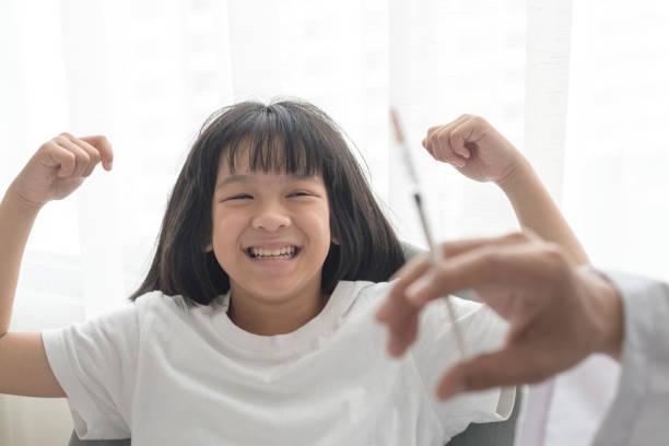 welt-impfwoche und international hpv bewusstsein tag konzept. starke glücklich gesundes asien kind mädchen lächelnd erste impfung gegen influenza oder grippe oder hpv-prävention mit arzt kinderarzt hand medizinische spritze im krankenhaus - immunsystem stärken stock-fotos und bilder