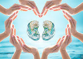 istock World Kidney Day design logo concept idea: Love heart shape symbolic sign of women human hands on blur blue turquoise clean aqua water background: Element of this image furnished by NASA 972347450