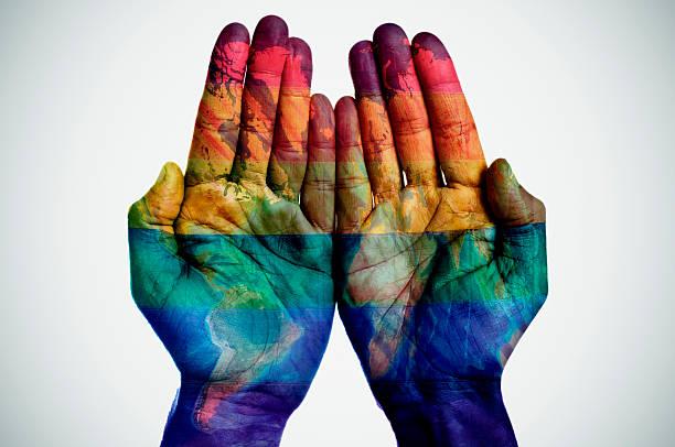 Mapa mundial y bandera del arco iris en las manos - foto de stock
