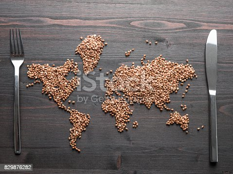 Buckwheat grain seeds are formed into world map on brown wooden desk.Knife and fork are placed on east and west sides.No people are seen in frame.Shot with a medium format camera from a high angle point in close up.Horizontal framing.