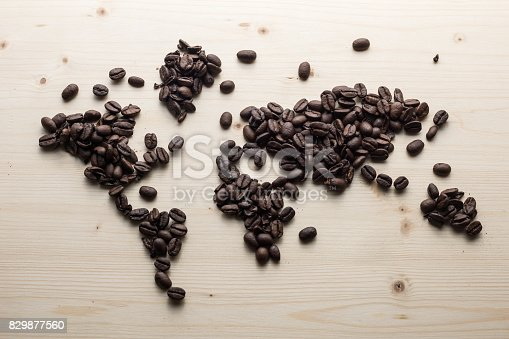 Coffee beans are transformed into world map on brown wooden desk.No people are seen in frame.Shot with medium format camera from a high angle point in close up.
