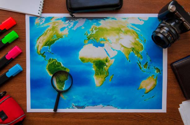 Carte mondiale sur une vue de dessus de table en bois. Concept voyages aventure vacances - Photo
