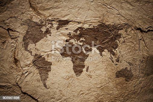 istock World Map on aged damaged paper 905961698