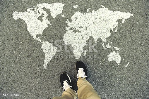 World map on an asphalt road. Top view of the legs and shoes. POV