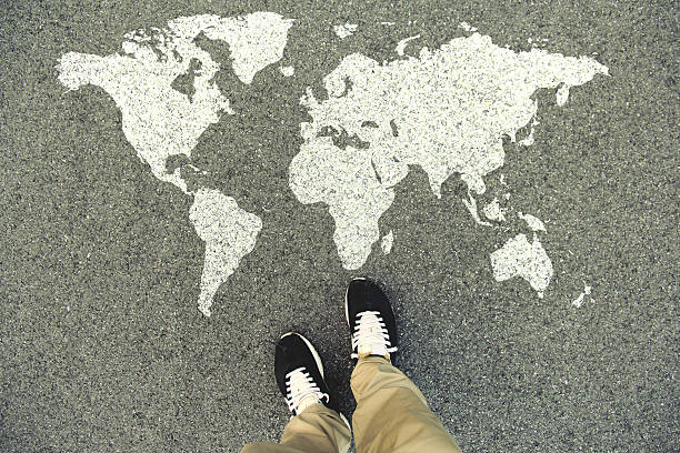 world map on an asphalt road - globus reisen stock-fotos und bilder