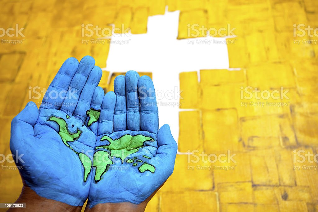 World Map painted on hands in front of Cross sign stock photo