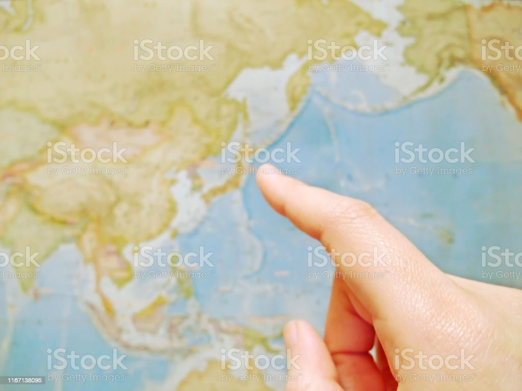 Pointing the world map with a finger.