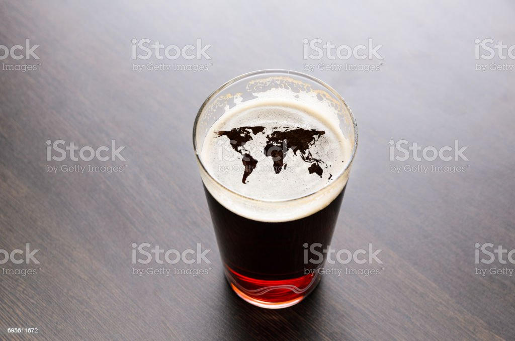 World map silhouette on beer glass stock photo