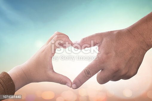 Father and son hands make heart shape over blurred nature background